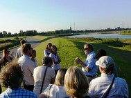 Thirteen participants standing on an embankment are listening to Manfred Meine at a field trip to Kreetsand